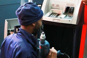 a-man-installing-an-atm-machine-atm-solutions