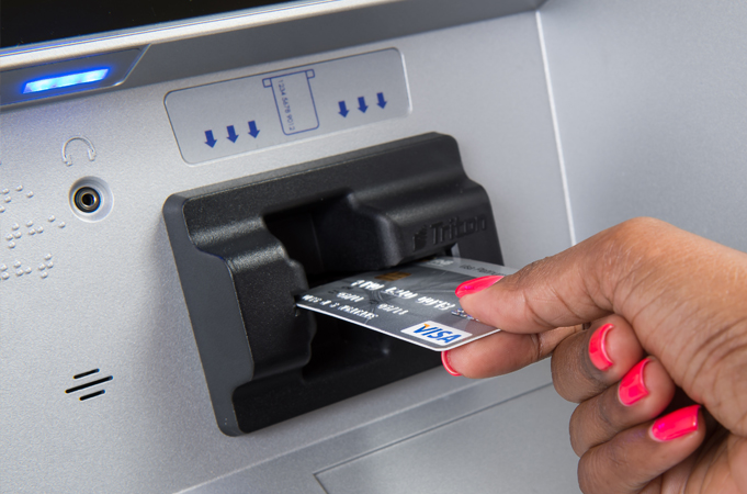 a-person-inserting-a-card-into-an-atm